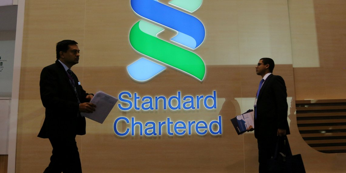 FILE PHOTO: People pass by the logo of Standard Chartered plc at the SIBOS banking and financial conference in Toronto, Ontario, Canada October 19, 2017. REUTERS/Chris Helgren
