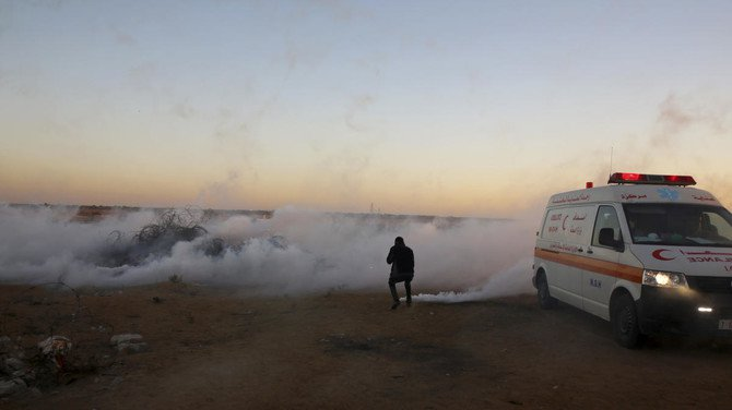 A protester tries to turn off one of a teargas canister fired by Israeli troops near the fence of the Gaza Strip border with Israel during a protest east of Khan Younis, southern Gaza Strip, Friday, Nov. 2, 2018. (AP)