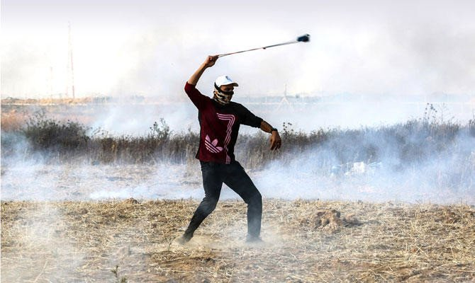 A Palestinian protester uses a slingshot to throw a stone toward Israeli forces during clashes in Gaza strip. (AFP/file photo)