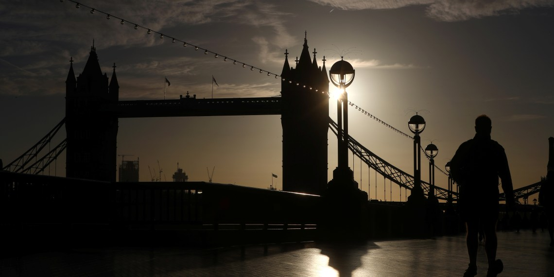 A man walks in the early morning autumn sunshine past Tower Bridge in central London, Britain, October 1, 2018. REUTERS/Hannah McKay