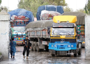 FILE PHOTO: An Afghan security guard stands while supply trucks carry containers for export at the Customhouse in Jalalabad, Afghanistan May 14, 2018. REUTERS/Parwiz