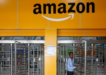 FILE PHOTO: An employee of Amazon walks through a turnstile gate inside an Amazon Fulfillment Centre (BLR7) on the outskirts of Bengaluru, India, September 18, 2018. REUTERS/Abhishek N. Chinnappa/File Photo
