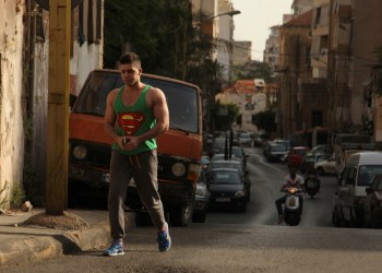 A man wearing a sleeveless shirt with the Superman logo walks along a street in Beirut, Lebanon May 2, 2016. REUTERS/Alia Haju - S1BETBTUSZAB