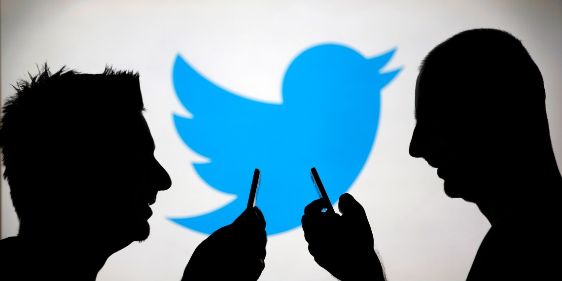 Men are silhouetted against a video screen with a Twitter logo as he poses with a Samsung S4 smartphone in this photo illustration taken in the central Bosnian town of Zenica, August 14, 2013. REUTERS/Dado Ruvic (BOSNIA AND HERZEGOVINA - Tags: BUSINESS TELECOMS)