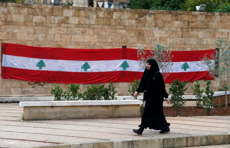 A woman walks past a Lebanese flag in Beirut, Lebanon, November 21, 2017. REUTERS/Mohamed Azakir
