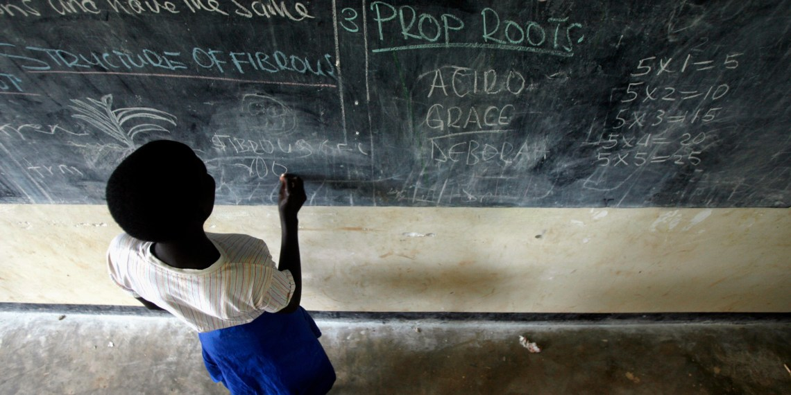 A girl writes the names of body parts on a chalkboard at an orphanage outside Gulu, Uganda, June 10, 2007. REUTERS/Edward Ou