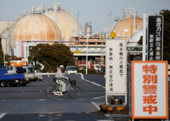 FILE PHOTO: A worker riding a bicycle passes the Fuji Oil Co.'s Sodegaura Refinery in Sodegaura, Japan February 8, 2017. Picture taken February 8, 2017. REUTERS/Issei Kato