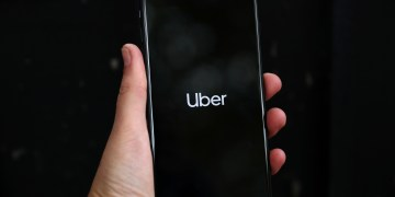 FILE PHOTO: Uber's logo is displayed on a mobile phone in London, Britain, September 14, 2018. REUTERS/Hannah Mckay