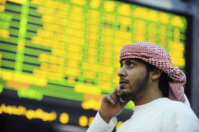 FILE PHOTO: An investor looks up at electronic boards displaying stock information at the ADX Abu Dhabi Securities Exchange stock market October 23, 2012. REUTERS/Ben Job