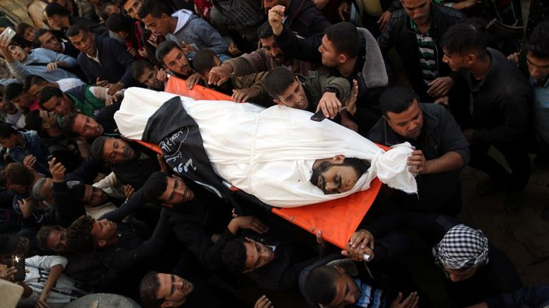 Mourners carry the body of Palestinian Khaled Qwaider, who was killed in Israeli air raid [Suhaib Salem/Reuters]