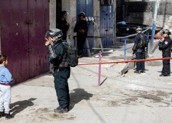 Members of the Israeli security forces form a security perimeter as excavators of the Jerusalem municipality (unseen) demolish over a dozen shops in the Arab-inhabited Shuafat refugee camp in Israeli-annexed East Jerusalem on November 21, 2018, which authorities said were built without a permit. (AFP)