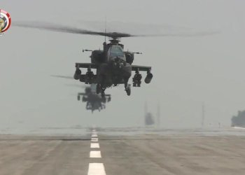 US-made Egyptian army Apache attack helicopters flying from an airfield. (AFP)