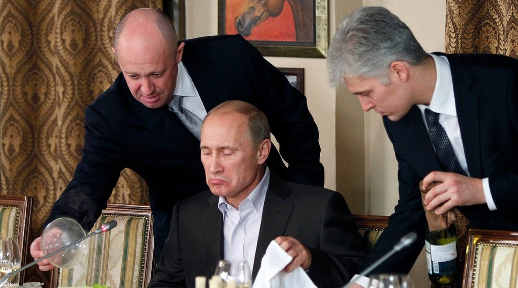 Yevgeny Prigozhin, left, and the Russian leader Vladimir V. Putin, center, at a dinner in 2011. Mr. Prigozhin was indicted by American prosecutors for his involvement in interfering in the 2016 presidential election.CreditCreditPool photo by Misha Japaridze