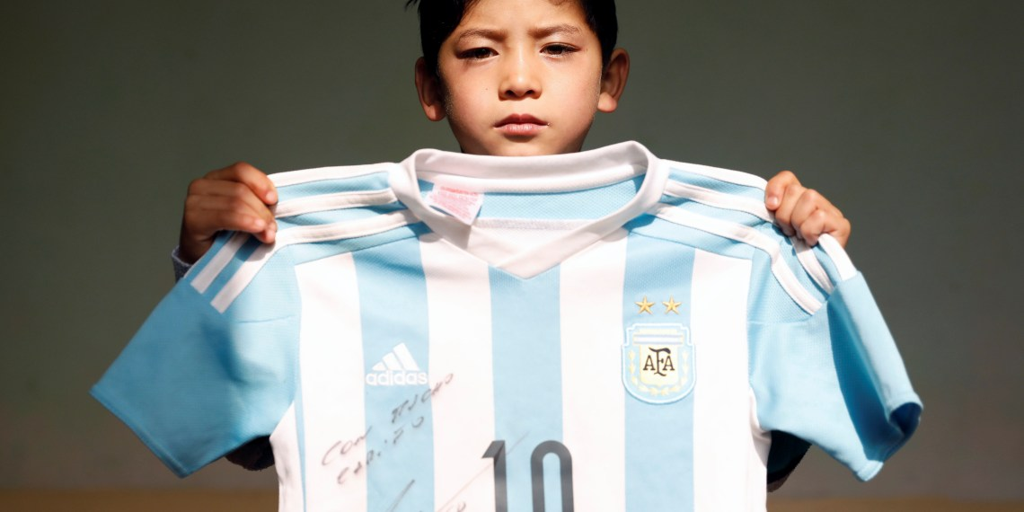 Murtaza Ahmadi, 7, an Afghan Lionel Messi fan, holds a T-shirt signed by Barcelona star Lionel Messi at his house in Kabul, Afghanistan December 8, 2018. REUTERS/Mohammad Ismail