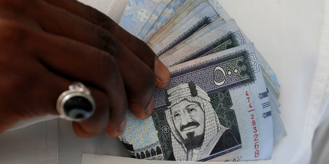 FILE PHOTO: A Saudi man shows Saudi riyal banknotes at a money exchange shop, in Riyadh, Saudi Arabia January 20, 2016. REUTERS/Faisal Al Nasser/File Photo