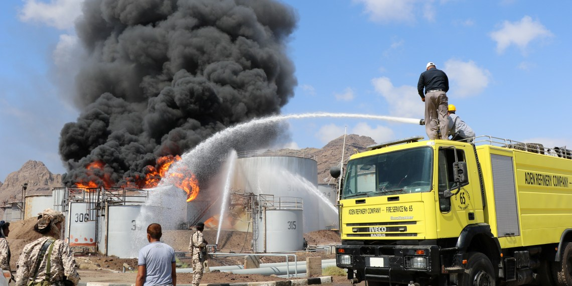 Firefighters try to cool down oil storage tanks adjacent to a tank engulfed by fire at the Aden oil refinery one day after an explosion in the refinery in Aden, Yemen January 12, 2019. REUTERS/Fawaz Salman
