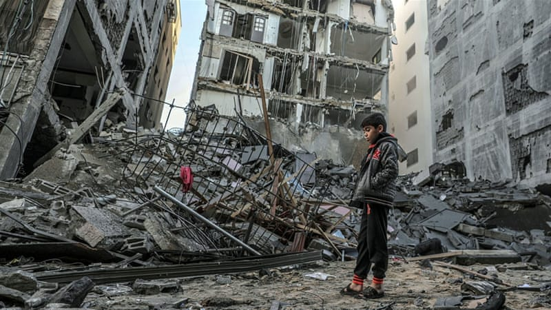 A Palestinian boy inspects the rubble of a destroyed residential building after an Israeli air strike in Gaza City in November)[Mohammed Saber