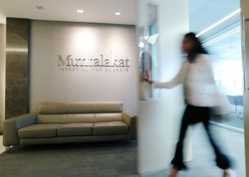 FILE PHOTO: Logo of Mumtalakat is seen as an employee walks out at their headquarters Manama, Bahrain February 21, 2018. REUTERS/Hamad I Mohammed