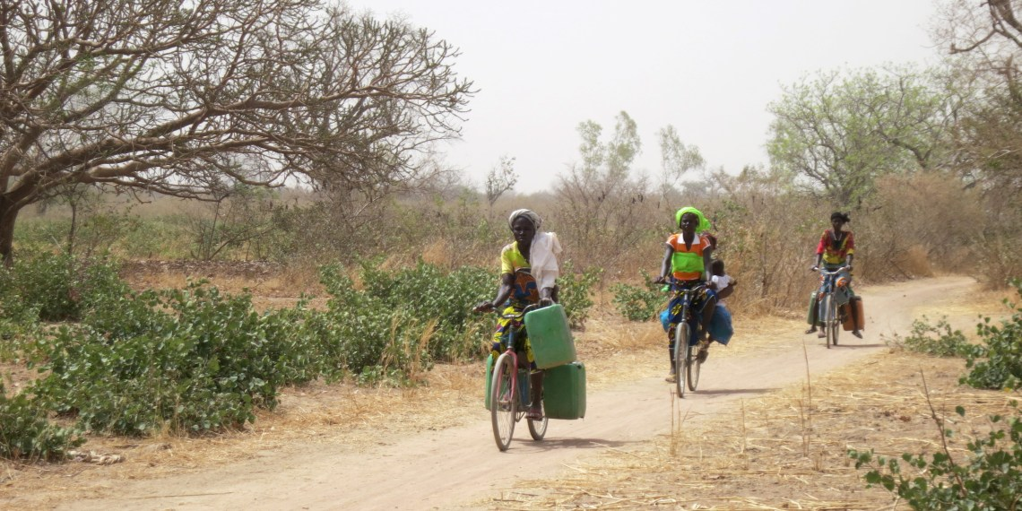 Women cycle with water tins towards the village of Bagare, Passore province, northern Burkina Faso, March 30, 2016     REUTERS/Zoe Tabary                            - GF10000391875