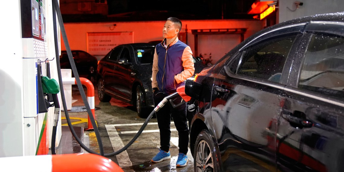 FILE PHOTO: A driver looks at the price as he fills the tank of his car at a gas station in Shanghai, China November 17, 2017. REUTERS/Aly Song