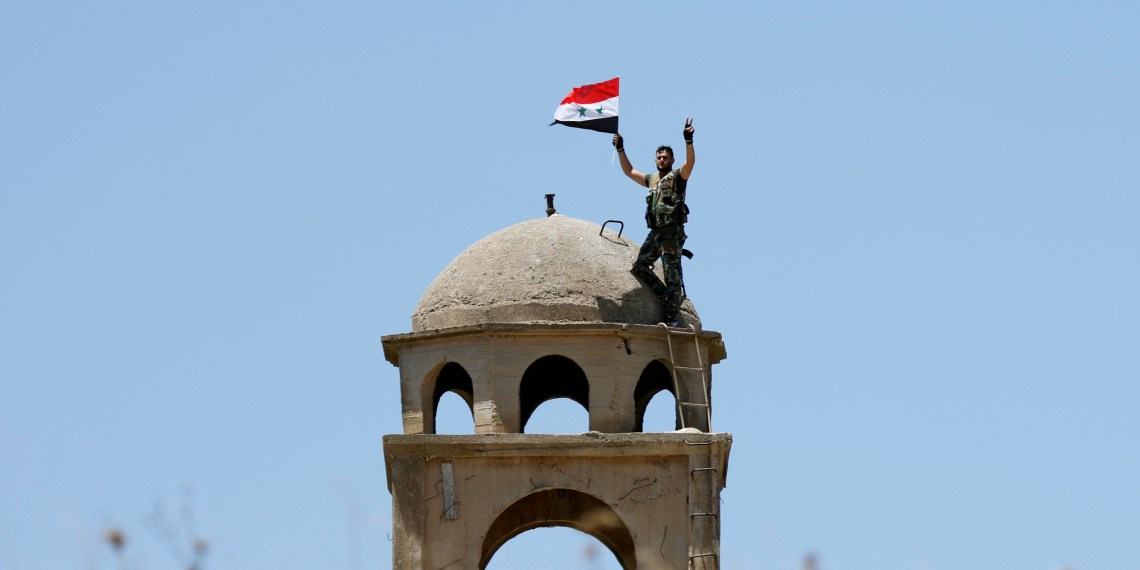 FILE PHOTO: A Syrian army soldier gestures as he holds a Syrian flag in Quneitra, Syria July 27, 2018. REUTERS/Omar Sanadiki/File Photo