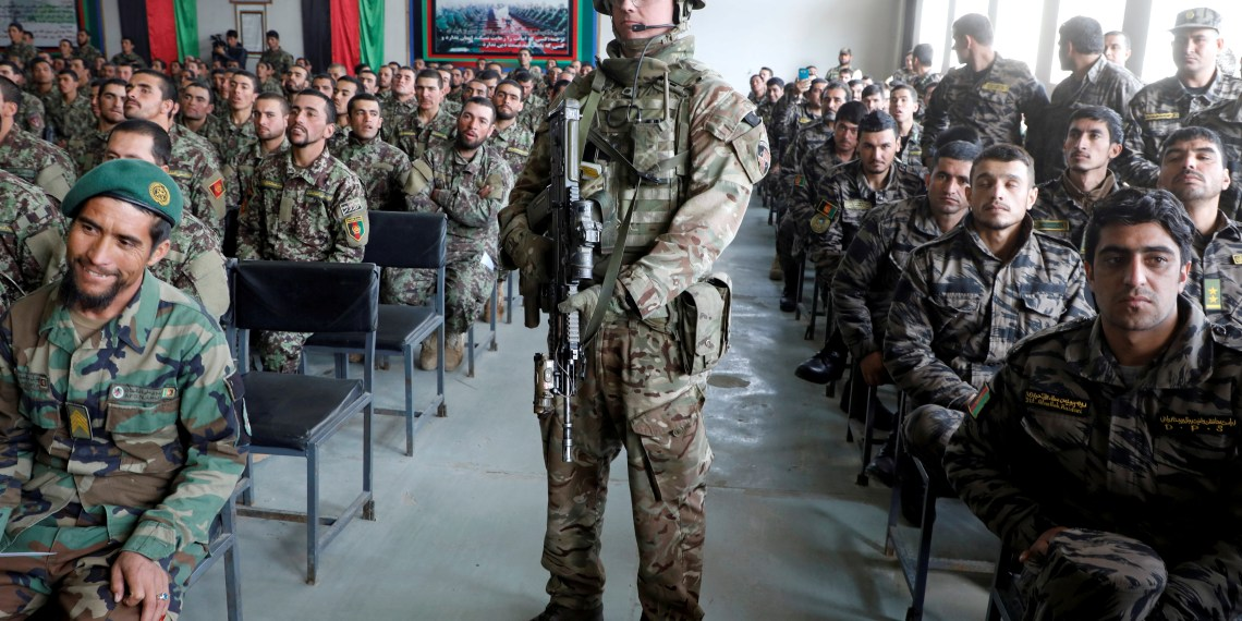 FILE PHOTO: Afghan National Army (ANA) soldiers attend their graduation ceremony while a NATO soldier stands guard at the Kabul Military Training Centre (KMTC) in Kabul, Afghanistan January 27, 2019. REUTERS/Omar Sobhani/File Photo