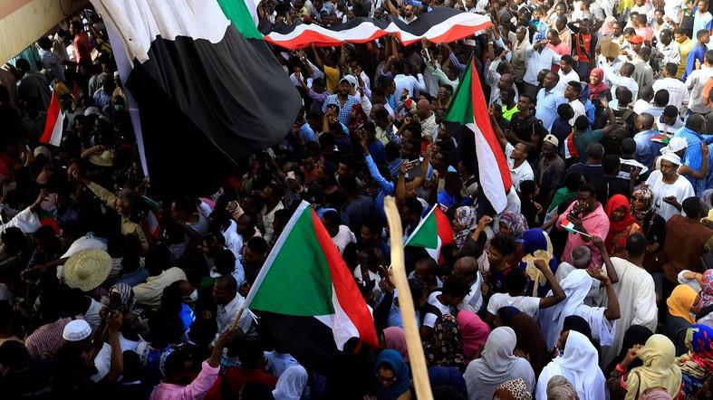Sudanese demonstrators wave their national flag as they attend a protest rally. (File photo: Reuters)