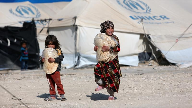 Children holding stacks of bread walk in al-Hol displacement camp in Syria [Ali Hashisho/Reuters]