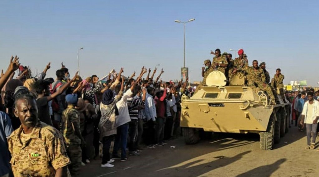 AFP | Sudanese protesters flash the victory sign at a passing military vehicle outside the army's headquarters in Khartoum on April 7, 2019.