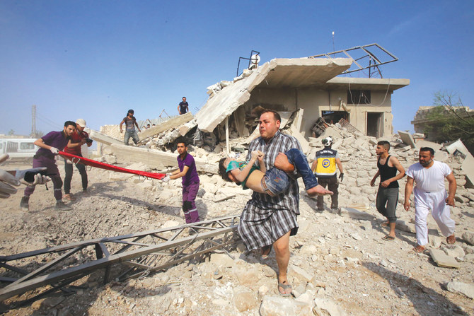 A man rescues a child while members of the Syrian civil defense, known as the White Helmets, search the area for survivors following a reported airstrike by regime forces and their allies in Idlib province on May 30, 2019. (AFP)