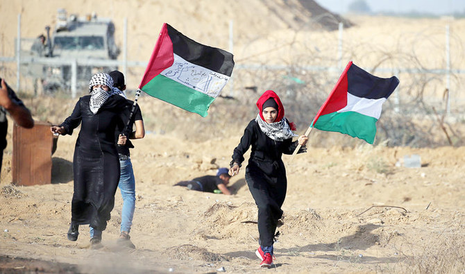 Women holding Palestinian flags run for cover from Israeli gunfire and tear gas during a protest at the Israel-Gaza border fence in Gaza on Friday. (Reuters)