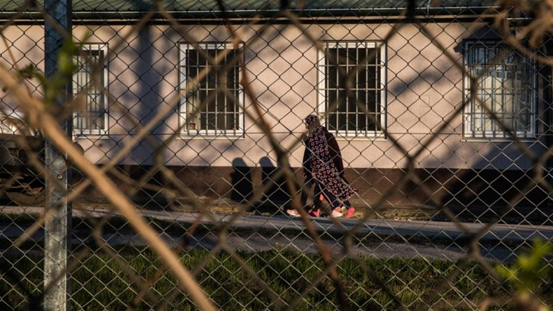 Two young Kosovar girls walk inside the compound of a detention centre near Pristina where they and 72 other children were held after returning [Valerie Plesch/Al Jazeera]