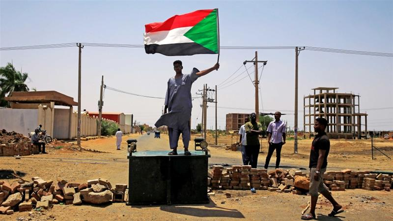 A Sudanese protester holds a national flag as he stands on a street barricade, demanding that the country's Transitional Military Council hand over power to civilians, in Khartoum on June 5 [Reuters]