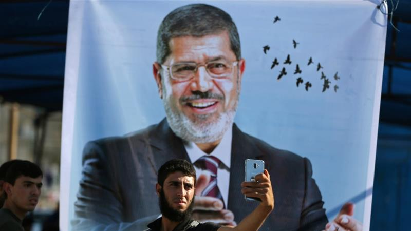A Palestinian man takes a selfie in front of a poster depicting former Egyptian president Mohamed Morsi at a mourning tent in Khan Younis in Gaza Strip [File: Ibraheem Abu Mustafa/Reuters]