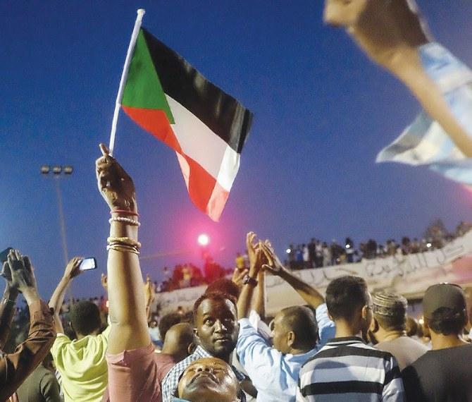 A Sudanese woman chants slogans and wave national flag in celebration, following a power-sharing agreement between ruling military council and the opposition in Khartoum on Friday. (Reuters)