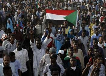 Sudanese protesters raise national flags as they rally in the capital Khartoum to mourn dozens of demonstrators killed last month in a brutal raid on a Khartoum sit-in, on July 13, 2019. (AFP)