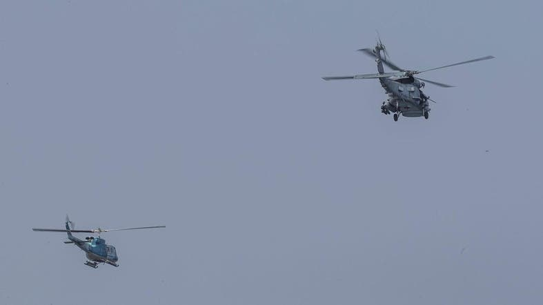 An MH-60R Sea Hawk helicopter with Helicopter Maritime Strike Squadron 46 (R) flies next to an Iranian helicopter (L) during USS aircraft carrier The Boxer (LHD-4) transit, through Strait of Hormuz in the Gulf of Oman. (Illustrative photo: AFP)