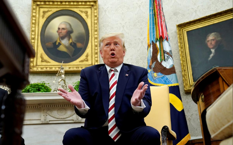 FILE PHOTO: U.S. President Donald Trump answers questions while sitting in front of paintings of former U.S. presidents George Washington and Thomas Jefferson during his meeting with Romania's President Klaus Iohannis in the Oval Office of the White House in Washington, U.S. August 20, 2019. REUTERS/Kevin Lamarque
