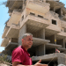 Muhammad Abu Tair in front of his demolished apartment building. Alex Levac