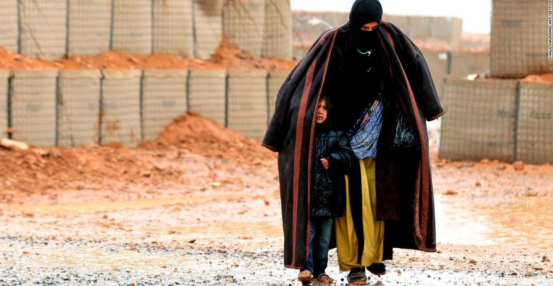 TOPSHOT - A Syrian refugee from the informal Rukban camp, which lies in no-man's-land off the border between Syria and Jordan in the remote northeast, walks in the rain, as she shelters a young child outside a UN-operated medical clinic immediately on the Jordanian-side on March 1, 2017. Conditions in the Rukban camp deteriorated sharply after Jordan sealed its border almost a year prior, following a cross-border jihadist attack that killed seven Jordanian border guards in June 2016. / AFP PHOTO / KHALIL MAZRAAWI (Photo credit should read KHALIL MAZRAAWI/AFP/Getty Images)