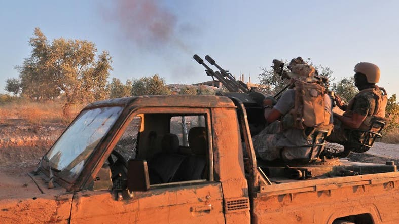 Fighters from Hayat Tahrir al-Sham (HTS) fire an anti-aircraft gun mounted on a pickup truck in Syria's southern Idlib province on August 7, 2019. (AFP)