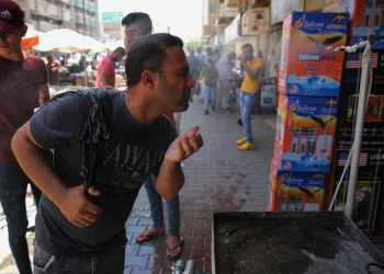 An Iraqi man uses a curbside shower to cool off during a heat wave in the capital Baghdad in June ( AFP/Getty )