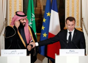French President Emmanuel Macron holds the arm of Saudi Arabia's Crown Prince Mohammed bin Salman during their press conference at the Elysee Palace in Paris, France, April 10, 2018. Yoan Valat/Pool via Reuters