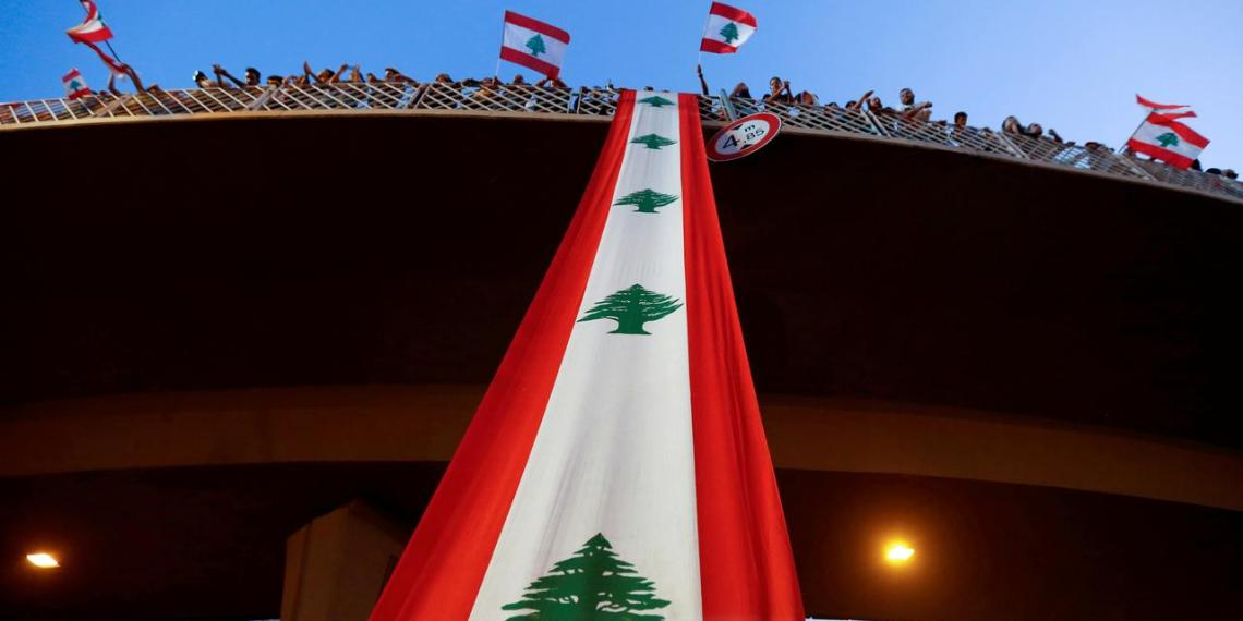FILE PHOTO: Demonstrators stand on a bridge decorated with a national flag during an anti-government protest along a highway in Jal el-Dib, Lebanon, October 21, 2019. REUTERS/Mohamed Azakir/File Photo