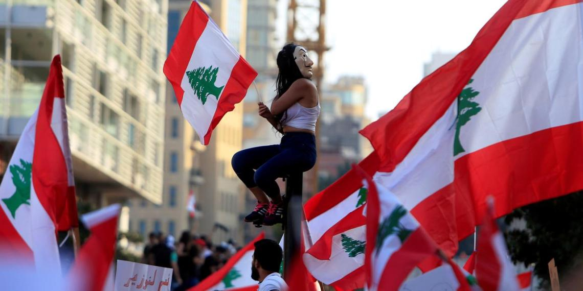 Demonstrators carry national flags during an anti-government protest in downtown Beirut, Lebanon October 20, 2019. REUTERS/Ali Hashisho