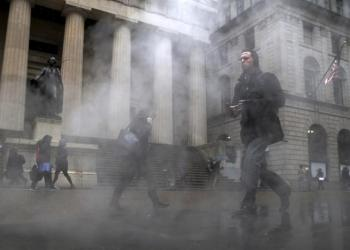 FILE PHOTO: Morning commuters walk through a steam cloud on Wall St. during a morning snow fall in New York's financial district March 4, 2016. REUTERS/Brendan McDermid