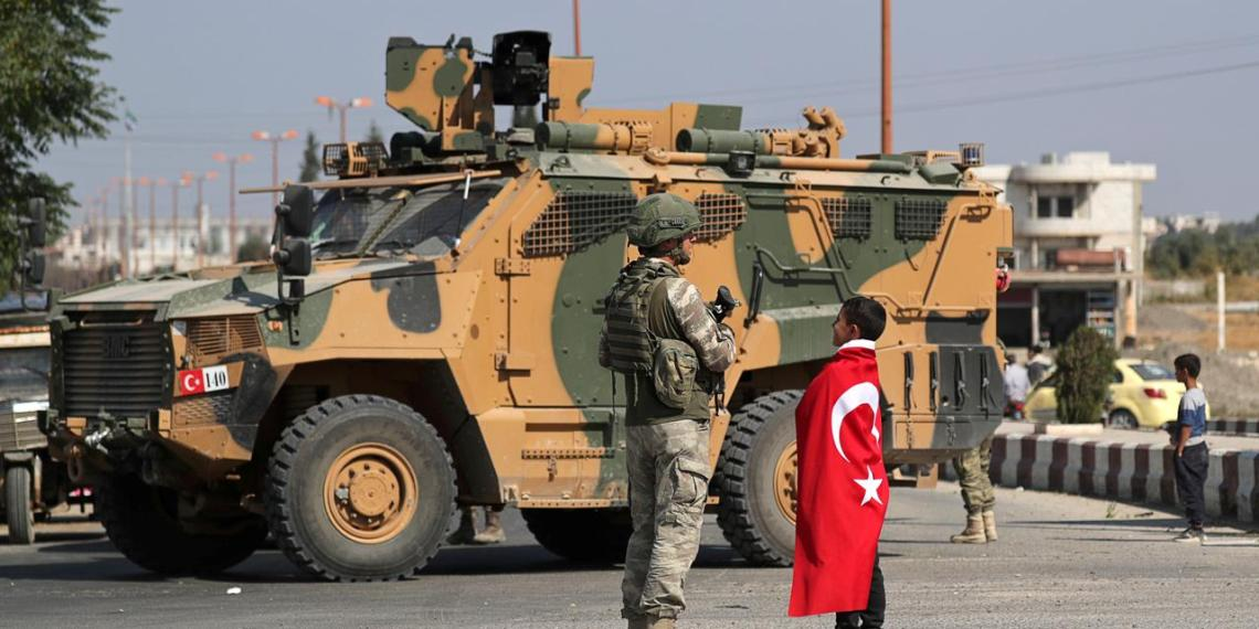 FILE PHOTO: A boy wearing a Turkish flag stands next to a Turkish soldier in the town of Tal Abyad, Syria October 23, 2019. REUTERS/Khalil Ashawi/File Photo