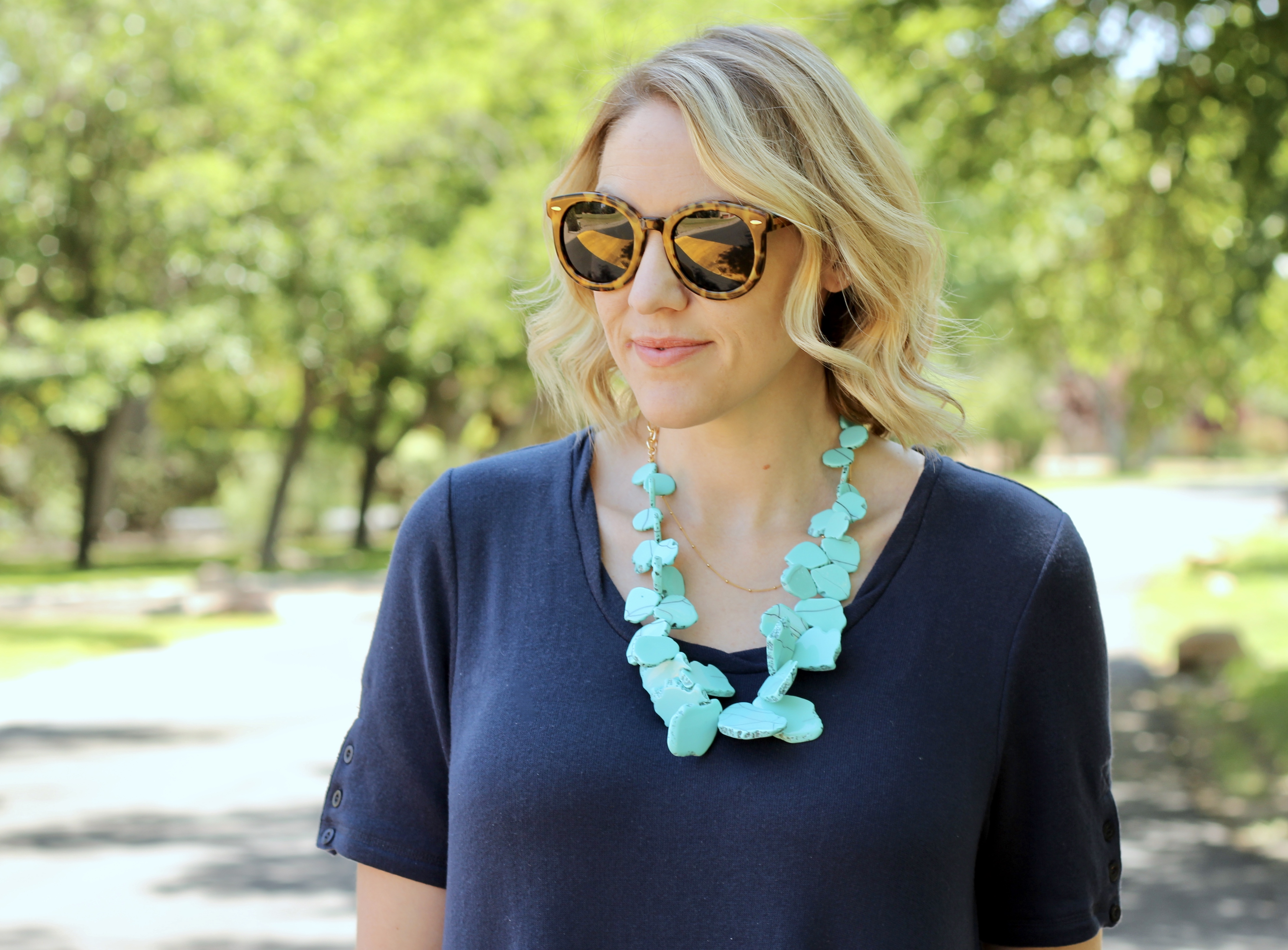 navy dress and a turquoise statement necklace