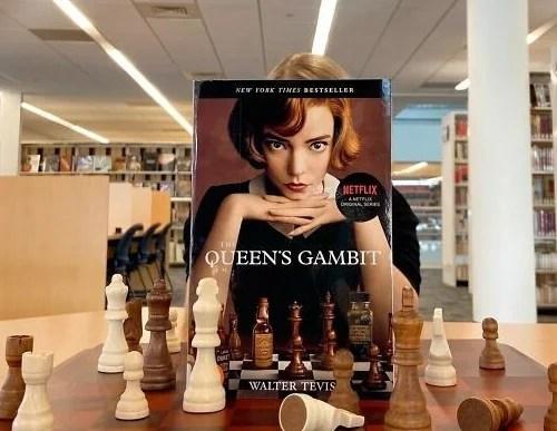 foto midiainteressante com capa de livros funcionarios entediados de livraria se divertem gamito da rainha livro da netflix beth harmon 1