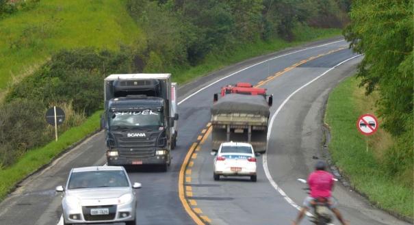 Caminhões, carros  e motocicleta em trecho não duplicado, na Serra